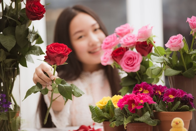 Asian woman preparing flowers for sale to customers in the shop