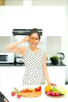 彼女の家の台所で健康的な食事を準備しているアジアの女性
