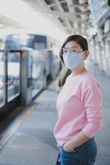 屋外に立っている保護フェイスマスクを着用する準備をしているアジアの女性