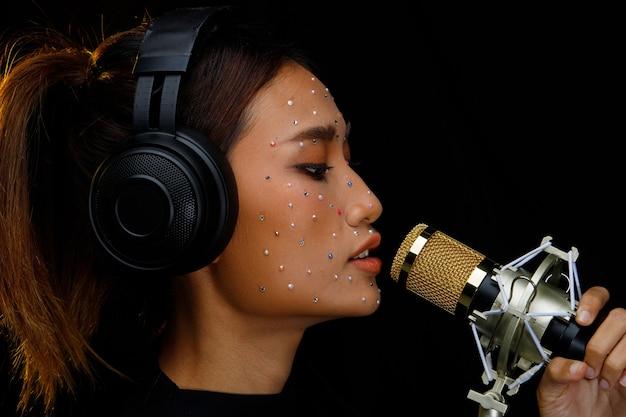 아시아 여자는 귀마개 헤드폰을 넣어 마이크 콘덴서를 매달려 큰 소리로 전원 소리를 노래합니다.