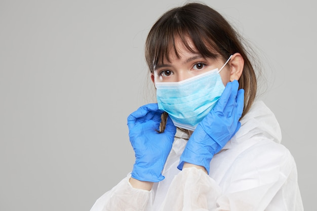 Asian woman puts on a protective mask and suit. protected against flu, ebola, tuberculosis, virus. personal protective equipment against biological hazard.