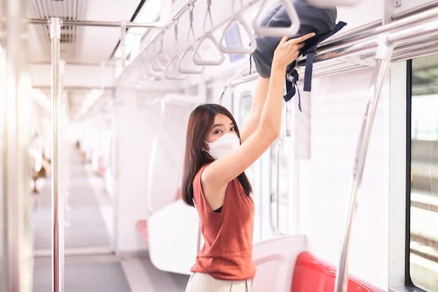 Asian woman putting her luggage on overhead shelf in train