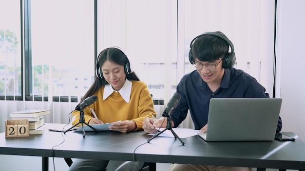 アジアの女性ラジオホストは、スタジオでのラジオライブのショー中にラジオ局で男性ゲストにインタビューしながらマイクに向かって身振りで示します。