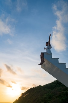 Asian woman raise arms up sit on top of wooden staircase with sunset sky in the background, victory, success concept