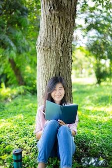 本を読んで公園で笑っているアジアの女性満足しているアジアの女性が公園で本を読んでいる