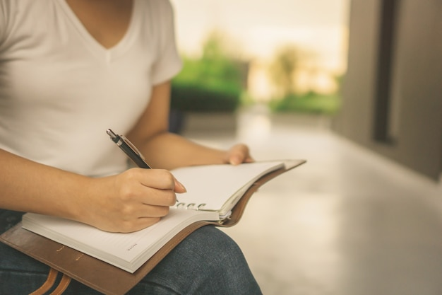 Азиатская женщина читает книгу в парке с небоскребами на заднем плане
