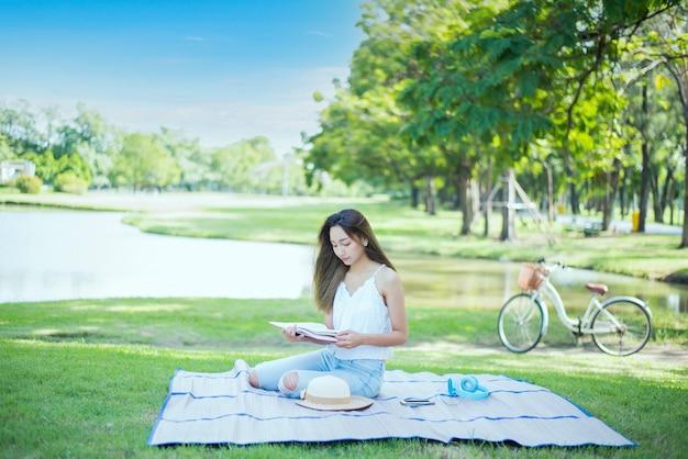 春の日に公園で一人で本を読んでいるアジアの女性。リラックスしてレクリエーション。休日の野外活動とライフスタイル。