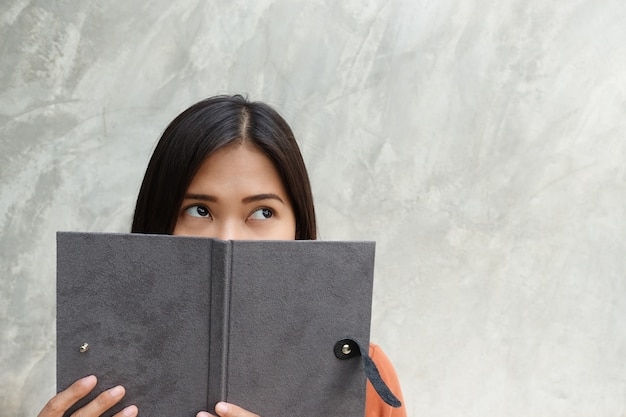 Asian woman reading a book on a gray background.