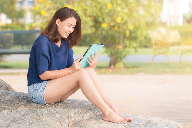 Asian woman reading a electronic book on a digital tablet.