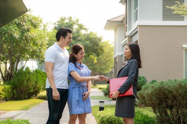 Азиатская женщина агент по операциям с недвижимостью, показывающий детали дома в своем досье молодой любительнице азиатских пар, которая ищет и заинтересована купить ее.