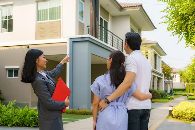 家の詳細を示すアジアの女性不動産ブローカーエージェント