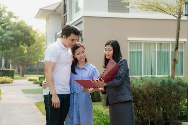 Asian woman real estate broker agent showing a house detail in her file to the young asian couple lover looking and interest to buy it.