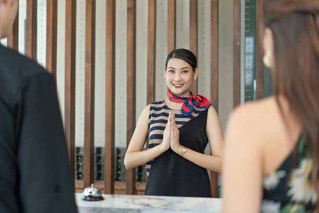 アジアの女性受付係は笑顔でホテルのカウンターでチェックインする外国人ゲストを歓迎することに敬意を表します
