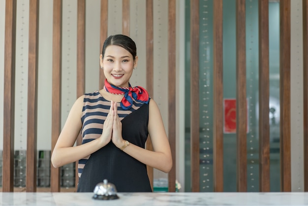 Asian woman receptionist smile and pay respect to welcome foreign guests checkin at hotel counter