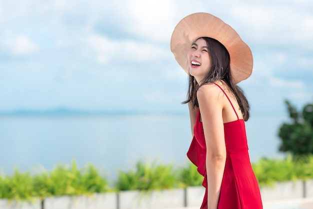 Asian woman in red dress enjoys her vacation in sunny day