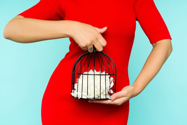 Asian woman in red dress holding a bird cage with a flower inside