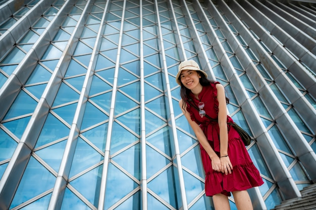 Asian woman in red dress at modern building, female girl with urban city lifestyle