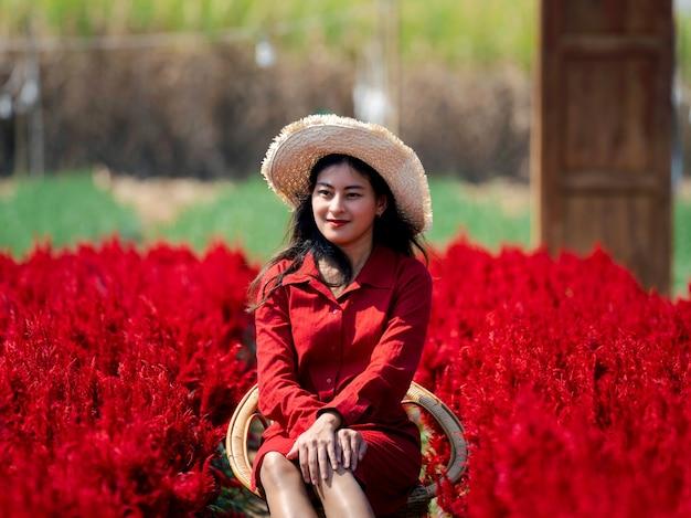 Asian woman in red dress sit in red flower garden