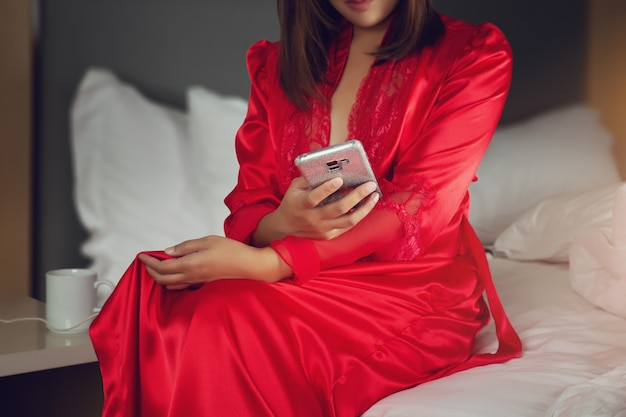 Asian woman in red satin robes using a mobile phone while sitting on a bed at night
