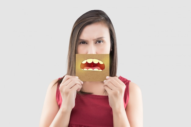 Asian woman in the red shirt holding a brown paper with the yellow teeth cartoon picture of his mouth on gray