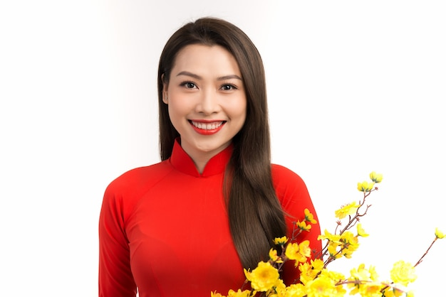Asian woman in red traditional vietnamese dress holding apricot blossom bouquet and smiling
