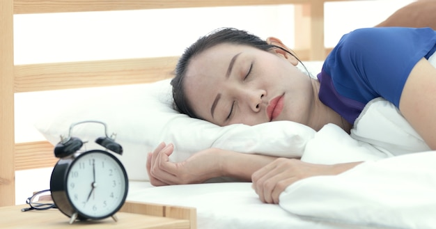 Asian woman refusing to wake up lying on her bed.