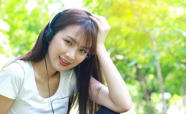 公園でスマホで楽しく音楽を聴きながらリラックスするアジア人女性。新世代の幸せな生活の概念
