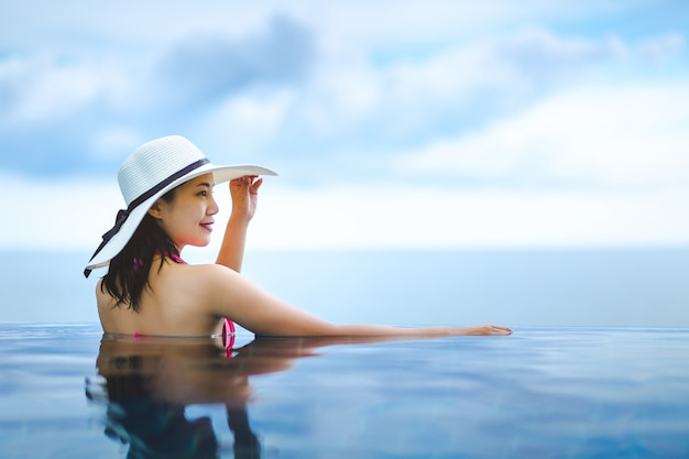 Asian woman relax in pool on beach