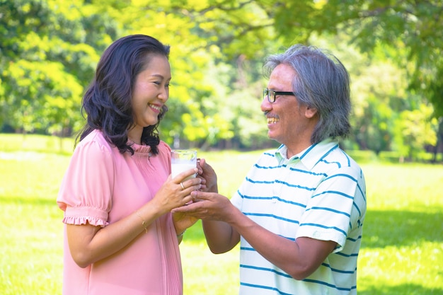 Asian woman relax time in park. a man sent milk for woman.