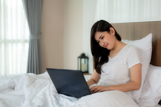 Asian woman relax using laptop and in bedroom.