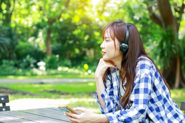 Азиатская женщина расслабляется, слушая музыку в наушниках