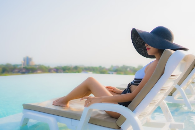 Asian woman relaxing by the swimming pool