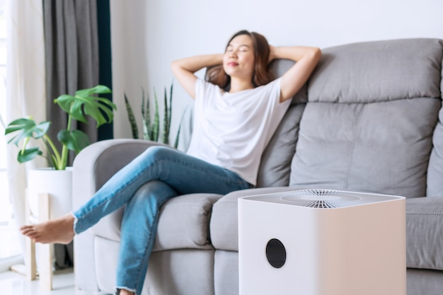 Asian woman relaxing on comfortable sofa at home with purifier beside.