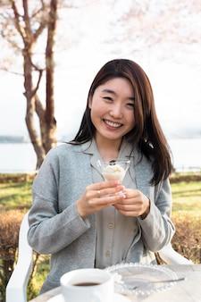 Donna asiatica che si distende all'aperto accanto a un albero di ciliegio