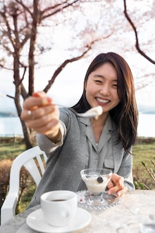 Asian woman relaxing outdoors next to a cherry tree