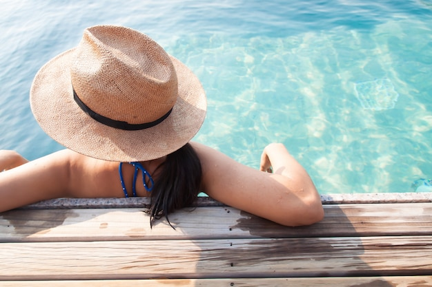 Asian woman relaxing in swimming pool, travel vacation concept