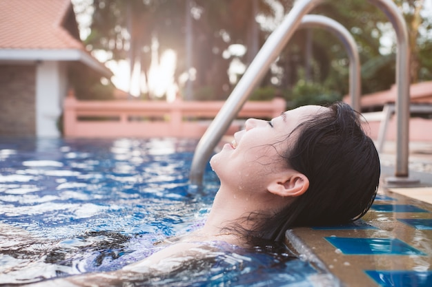 Asian woman relaxing in the swimming pool with happiness and emotions.