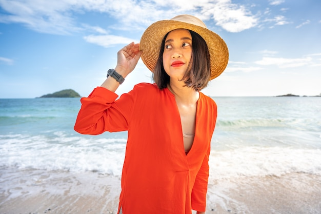 Asian woman relaxing on the tropical sand beach with straw hat and blue sea background.