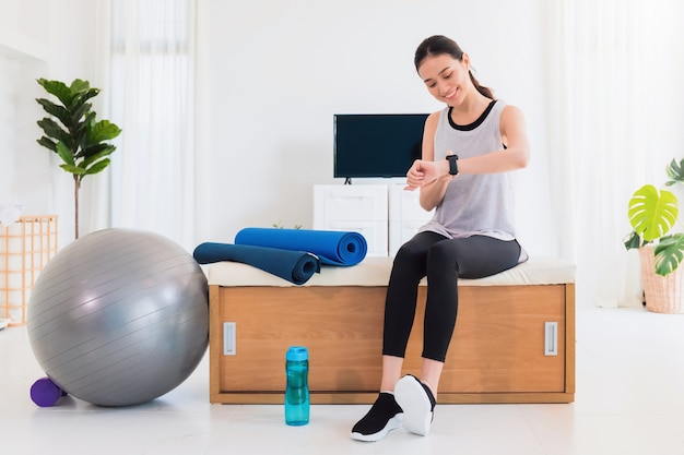 Asian woman resting and using smart watch after play yoga and exercise at home background.