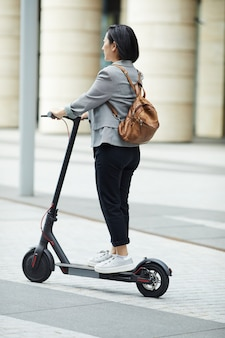 Азиатская женщина верхом электрический скутер