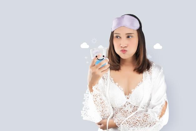 Азиатская женщина полоскает рот жидкостью для полоскания рта после чистки зубов после пробуждения, чтобы начать утро.