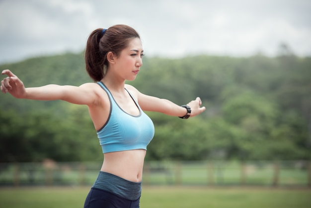 Asian woman runner warm up and exercising in the stadium.