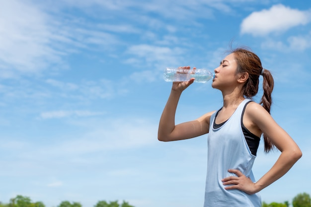 Asian woman runners are drinking water. after training.