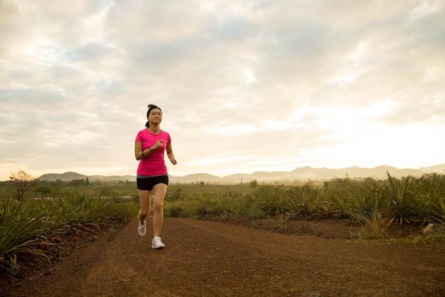 아침에 시골에서 달리는 아시아 여성.