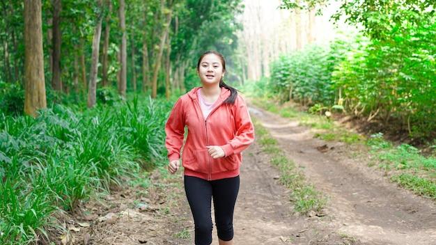 재킷을 입고 숲에서 실행 아시아 여자
