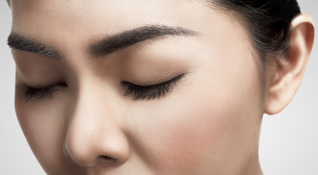Asian woman's eyes closed