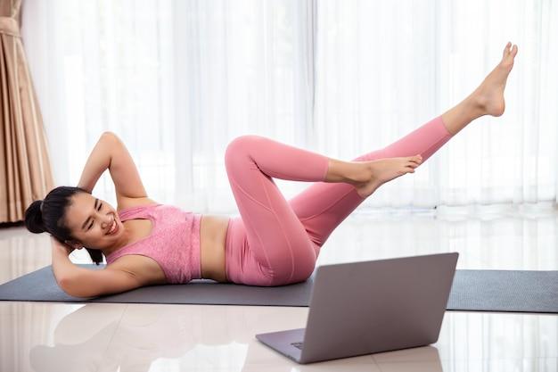 집에서 아시아 여성의 피트니스 운동. 그녀는 노트북에서 비디오를보고 거실에서 훈련하는 새로운 운동을 배우고 있습니다.