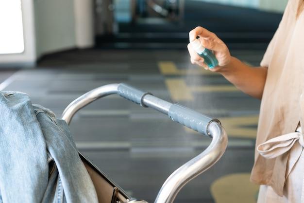 コロナウイルスまたはcovid-19保護のためのアルコールスプレーで空港カートを消毒するアジアの女性の手。