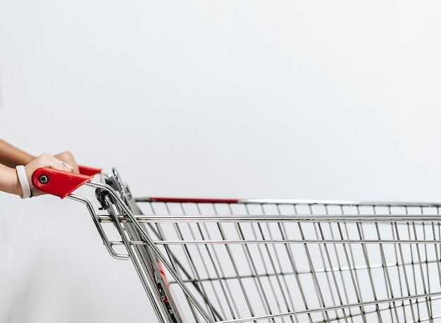 An asian woman's hand with an empty shopping cart.this image is soft focus.