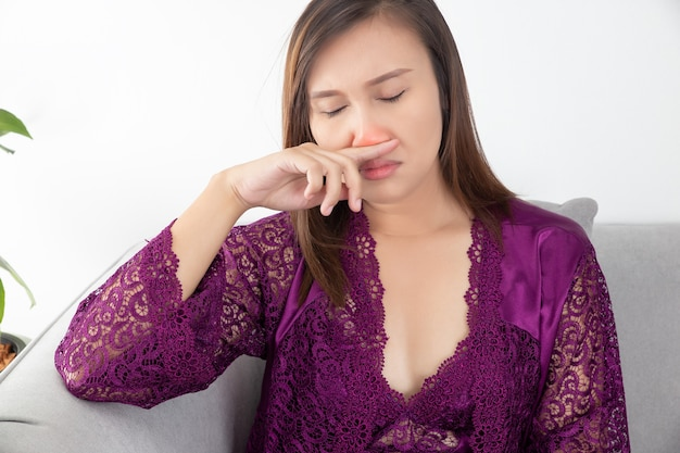 Asian woman's stuffy nose, a girl has an allergy to room dust. Premium Photo
